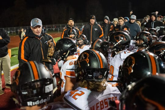 Almont head coach James Leusby holds the MHSAA Division5 district champion trophy as he addresses the team after their 22-20 victory over Marine City Friday, Nov. 8, 2019, at East China Stadium.