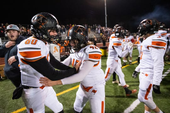 Almont's Corey Webster (42) celebrates with Shane Vandenbossche after Almont defeated Marine City 22-20 in the MHSAA Division 5 district final match Friday, Nov. 8, 2019, at East China Stadium.