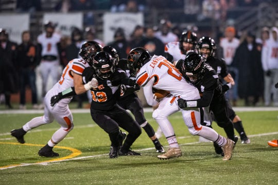 Almont's Jacob Castillo (26) is tackled by players from Marine City during the MHSAA Division 5 district final Friday, Nov. 8, 2019, at East China Stadium.
