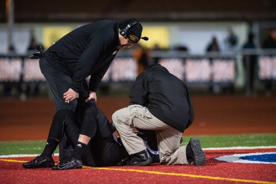 Marine City coaching staff tend to Angelo Patsalis after he is injured during a play in the MHSAA Division 5 district final against Almont Friday, Nov. 8, 2019, at East China Stadium.