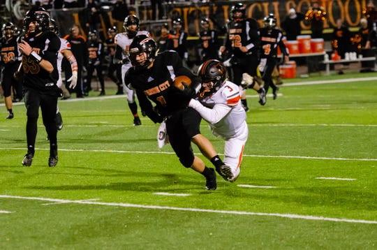 Marine City's Charles Tigert (1) is grabbed by Almont's Caleb Weigand as he runs with the football in the fourth quarter of the MHSAA Division 5 district final match Friday, Nov. 8, 2019, at East China Stadium.