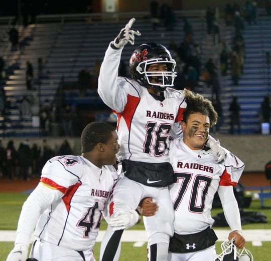 Port Jervis', from lot, Isaac Cayetano, Elijah Shearn and Tishawn Featherstone celebrate winning the Section IX Football Championship over Marlboro in Middletown on November 8, 2019.