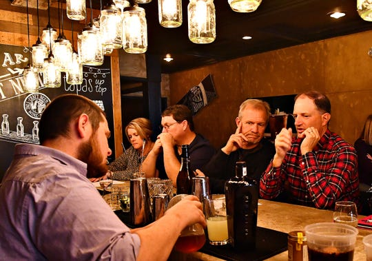 From right, John Bowman, of Manchester Township, and Scott Lussier, of Lancaster look on as Regional General Manager Jacob Dopp, of O.N.E. Hospitality Group, left, teaches a cocktail-making class at Tutoni's Restaurant in York City, Saturday, Nov. 9, 2019. Dawn J. Sagert photo