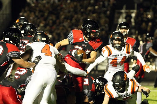 Tate Johnson of Brandon Valley steps over several Washington defenders during Friday's 11AAA semifinal game in Brandon.