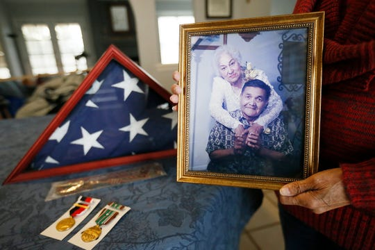 Cynthia Franco shows service memorabilia from her late father Amado L. Castro and a 55th anniversary photo of him and her mother Friday, Nov. 8, at her home in El Paso. Franco is trying to get Purple Heart for her father, Amado, who is deceased.