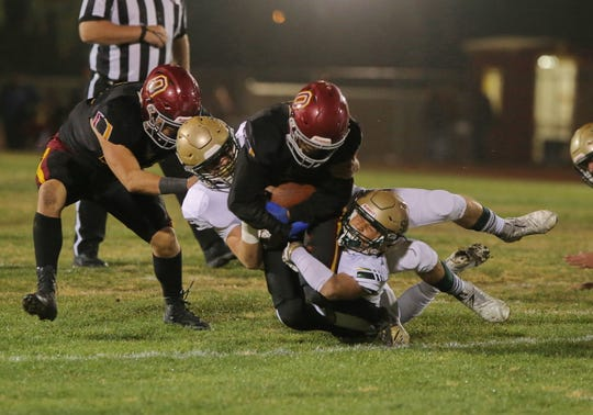 St. Bonaventure High's Isaac Thorpe (on ground) and another player brings down by Oxnard's Fred Vasquez during the first quarter of their CIF-SS Division 5 first-round game on Friday night. Oxnard won, 40-13.