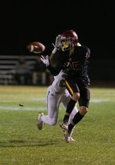 Oxnard High's Marcus Bustillos makes a reception in front of St. Bonaventure High's Ryeon Morales during the first quarter of their CIF-SS Division 5 first-round game on Friday night. Oxnard won, 40-13.