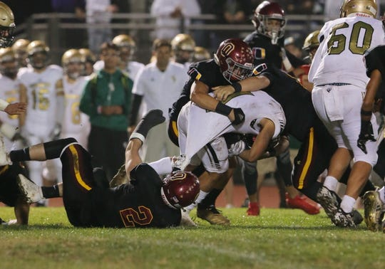 St. Bonaventure High's James Arellanes is stopped by Oxnard's Grant Ennis (2), Anthony Lopez and another player during the second quarter of their CIF-SS Division 5 first-round game on Friday night. Oxnard won, 40-13.