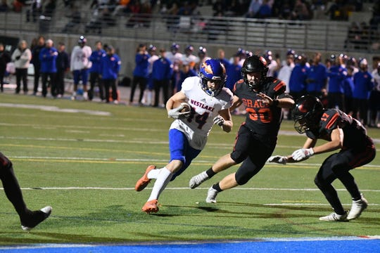 Westlake's Cooper Wallace heads into the end zone to complete a touchdown reception against Grace Brethren in a Division 3 first-round game Friday night at Westlake High. Grace Brethren won, 42-28.