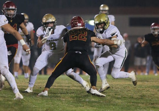 St. Bonaventure High's Benny Harrold is stopped at the line of scrimmage by Oxnard's Tytus Hutchinson during the second quarter of their CIF-SS Division 5 first-round game on Friday night. Oxnard won, 40-13.