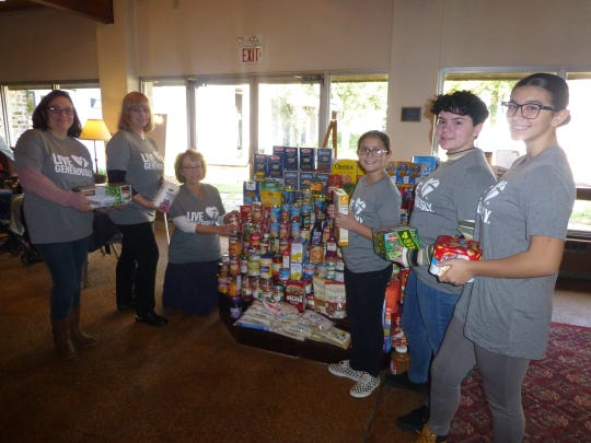 Dawn Amari (kneeling), who led the Redeemer Lutheran Church of Vineland team which collected more than 500 food items for the Vineland Ministerium Food Bank, organizes donations along with, (standing, from left) Donna Matlack, Tammy Oliva, Jamie Gonzalez, Angelina Oliva and Rachel Gonzalez.