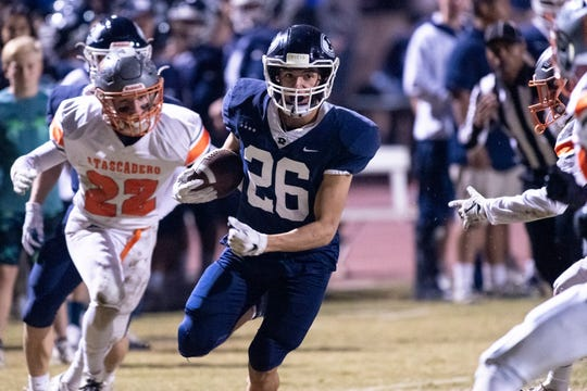 Redwood's Caden Shafer runs ahead of Atascadero's Cael Cooper in a Central Section Division II high school football game on Friday, November 8, 2019.