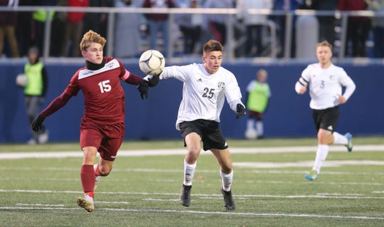 Ossining's Nolan Lenaghan (15) works the ball against Monroe-Woodbury's Dylan Tarasenko (25) in the NYSPHSAA class AA boys soccer regional finals at Pace University in Pleasantville on Saturday, November 9, 2019.