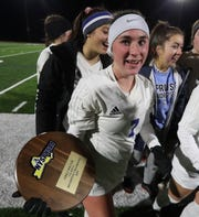 Pearl River's Kate McNally (7) holds the plaque after defeating Minisink in the class A girls soccer state quarterfinal match at Goshen High School on Friday, November 8, 2019.