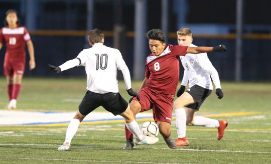 Ossining's Andrew Inga (8) works against Monroe-Woodbury's Jesse Schwartz (10) during their 1-0 win in the NYSPHSAA class AA boys soccer regional finals at Pace University in Pleasantville on Saturday, November 9, 2019.