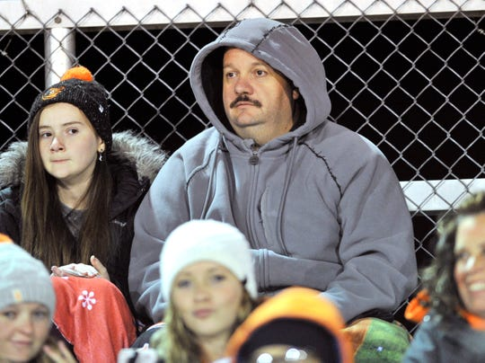 Delmar face in the crowd watching action out on the field in game with Woodbridge.