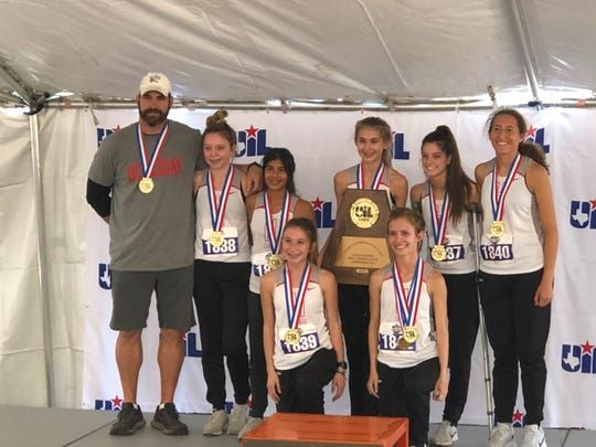 The Holliday girls cross country team poses on the medal stand after winning the Class 3A state team title Saturday, Nov. 9, in Round Rock.