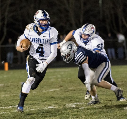 Zanesville's quarterback, Ben Everson, runs past Granville's defense in a first round playoff game Friday night. Granville won the game 41-7.