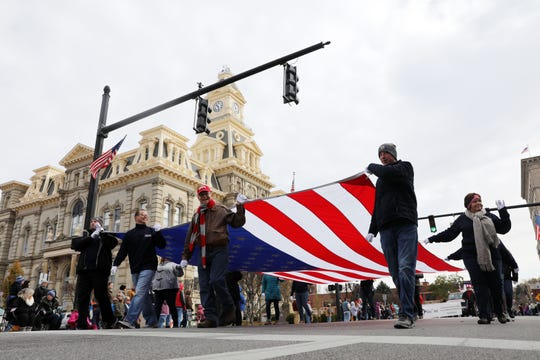 Community members carried a large American flag during Zanesville's annual Veterans Day parade.