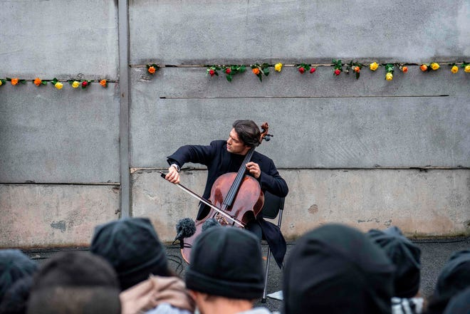 French cellist Gautier Capucon performs at the Berlin Wall memorial, after official guests attended celebrations of the 30th anniversary of the fall of the Berlin Wall, on November 9, 2019 in Bernauer Strasse in Berlin. Germany celebrates 30 years since the fall of the Berlin Wall ushered in the end of communism and national reunification, as the Western alliance that secured those achievements is increasingly called into question. x