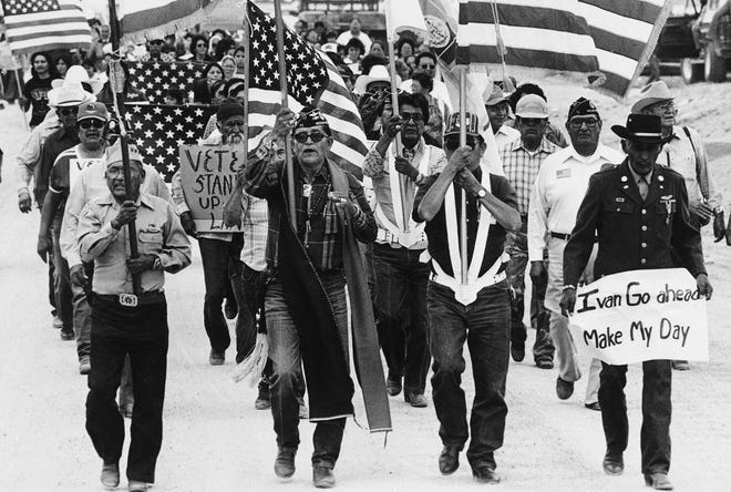 "In this July 8, 1986, file photo, World War II Navajo veterans and supporters march through the reservation in a show of solidarity against giving up any of their land to the Hopis in Arizona. ""The Warrior Tradition,"" a new film set to air on most PBS stations Monday, Nov. 11, 2019, examines the history of Native Americans in the U.S. military since World War I. (AP Photo/Jeff Robbins, File) ORG XMIT: FX601"