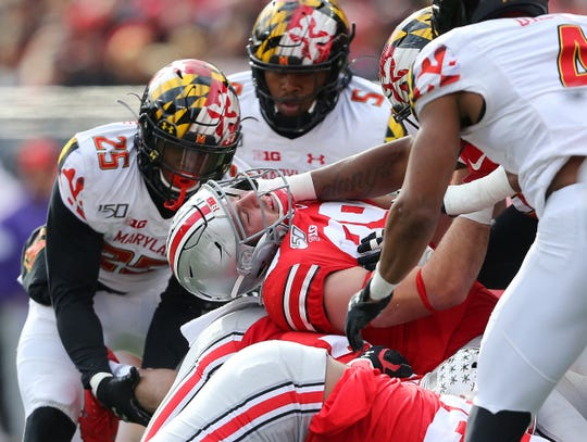 Ohio State Buckeyes tight end Luke Farrell  has his head bent back by a Maryland Terrapins defender during the third quarter at Ohio Stadium.
