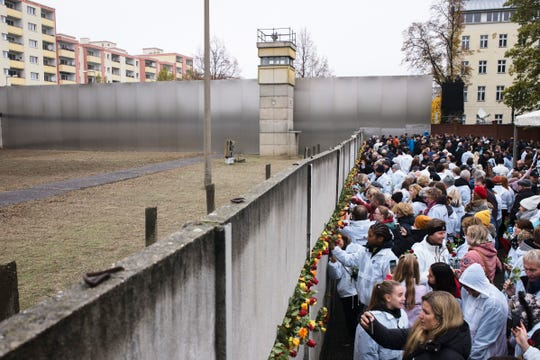 People stuck flowers in remains of the Berlin Wall during a commemoration ceremony to celebrate the 30th anniversary of the fall of the Berlin Wall at the Wall memorial site at Bernauer Strasse in Berlin, Saturday, Nov. 9, 2019.