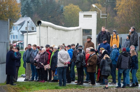 Visitors stand at the East German - West German borderline, a part of a German open-air museum in Moedlareuth, Germany. Nov. 9, 2019.