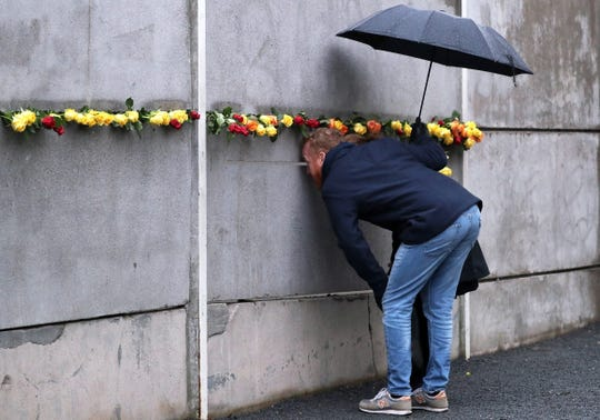 A couple look through a gap in the Wall Memorial after the end of the official celebrations of the 30th anniversary of the fall of the Berlin Wall at the Berlin Wall Memorial site along Bernauer street in Berlin, Germany on Nov. 9, 2019.