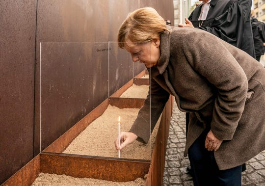 German Chancellor Angela Merkel places a candle at the Berlin Wall Memorial during the central commemoration ceremony for the 30th anniversary of the fall of the Berlin Wall, on Nov. 9, 2019 at the Berlin Wall Memorial at Bernauer Strasse in Berlin.
