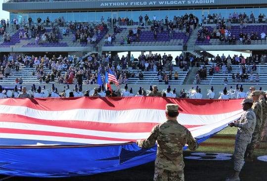 "Military personnel ""wave"" a huge American flag during the playing of the national anthem before Saturday afternoon's football game at Wildcat Stadium. Nov. 9 2019"