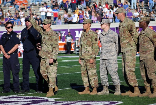 Col. Jeffrey Menasco waves to home-side fans at Wildcat Stadium after being introduced during Saturday's football game. To his left is Col. Ed Sumangil, Dyess Air Force Base commander. Menasco commands the 317th Airlift Wing while Sumangil commands the 7th Bomb Wing. Nov. 9 2019