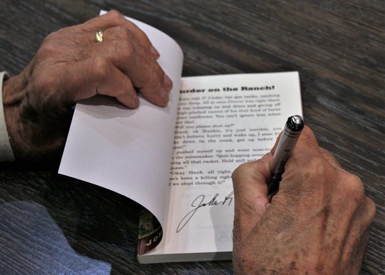 "Author John Erickson signs his ""John Hancock"" to copies of his books Sunday at Texas Star Trading Co., which was full of ""Hank the Cowdog"" fans."