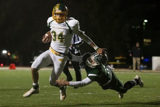 Burr and Burton quarterback Joseph McCoy (34) runs past St. Johnsbury's Wilder Hudson (11) during the DI football championship game between St. Johnsbury Hilltoppers and the Burr and Burton Bulldogs at Rutland High School on Saturday evening November 9, 2019 in Rutland, Vermont.