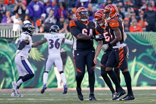 Cincinnati Bengals quarterback Ryan Finley (5) is helped off the field by offensive tackle John Jerry (64) and wide receiver Auden Tate (19) as the Ravens celebrate a touchdown following a sack-fumble given up by Finley in the third quarter of the NFL Week 10 game between the Cincinnati Bengals and the Baltimore Ravens at Paul Brown Stadium in downtown Cincinnati on Sunday, Nov. 10, 2019. The Bengals fell 49-13 to the Ravens and remain winless on the season.