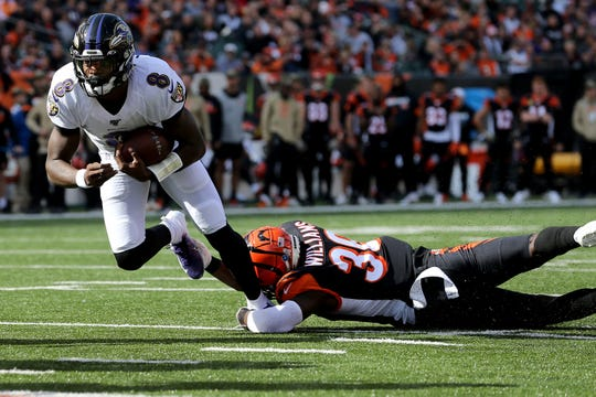 Baltimore Ravens quarterback Lamar Jackson (8) is tackled by Cincinnati Bengals strong safety Shawn Williams (36) in the first quarter of a Week 10 NFL game, Sunday, Nov. 10, 2019, at Paul Brown Stadium in Cincinnati.