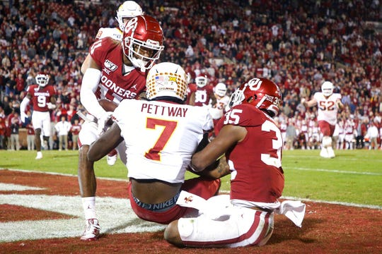 Oklahoma cornerback Parnell Motley (11) intercepts a pass on a 2-point conversion attempt intended for Iowa State wide receiver La'Michael Pettway (7), while Oklahoma linebacker Nik Bonitto (35) defends during an NCAA college football game Saturday, Nov. 9, 2019, in Norman, Okla. (Ian Maule/Tulsa World via AP)