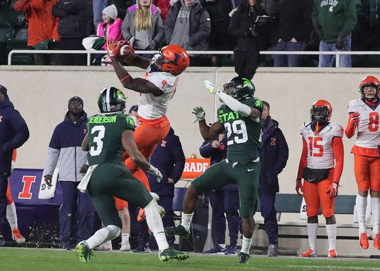 Illinois receiver Josh Imatorbhebhe makes a catch on fourth down against Michigan State Spartans cornerback Shakur Brown (29) and safety Xavier Henderson (3) to set up the winning touchdown Saturday, Nov. 9, 2019 at Spartan Stadium in East Lansing.