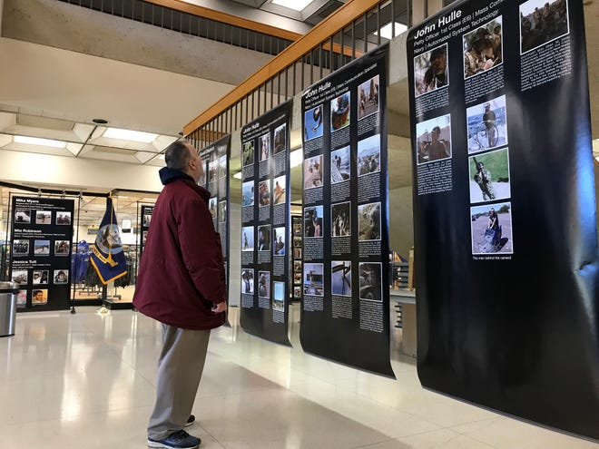 Sean Newberry of Warren, a Macomb Community College student, stops Nov. 8, 2019 to look at a photo exhibit by fellow students of their experiences in the Armed Forces to recognize Veterans Day. Newberry was looking at the display at the college's South Campus in Warren.