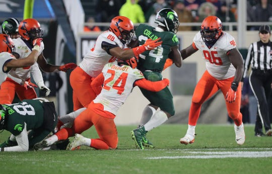 Michigan State Spartans running back Elijah Collins (24) is tackled by Illinois Fighting Illini defensive lineman Keith Randolph Jr. (88) and linebacker Dawson DeGroot (24) during second half action Saturday, November 9, 2019 at Spartan Stadium in East Lansing, Mich.