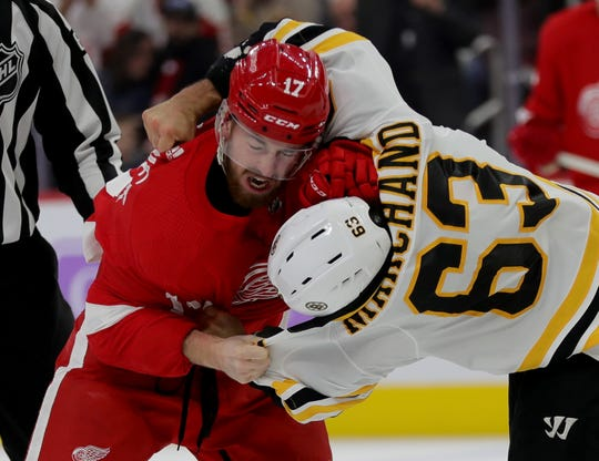 Detroit Red Wings defenseman Filip Hronek and Boston Bruins center Brad Marchand fight during the second period Nov. 8, 2019 at Little Caesars Arena.