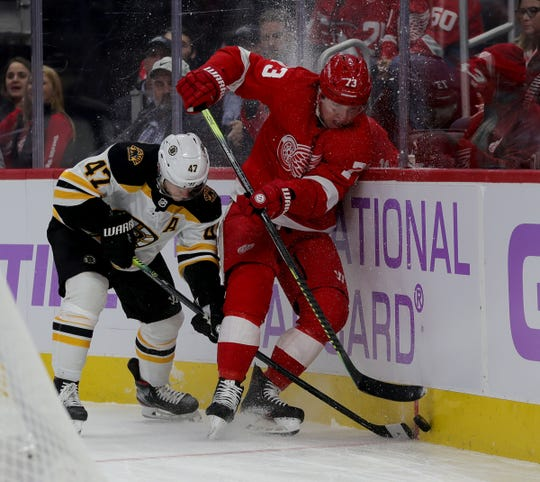 Detroit Red Wings left wing Adam Erne goes for the puck against Boston Bruins defenseman Torey Krug during the first period Nov. 8, 2019 at Little Caesars Arena.