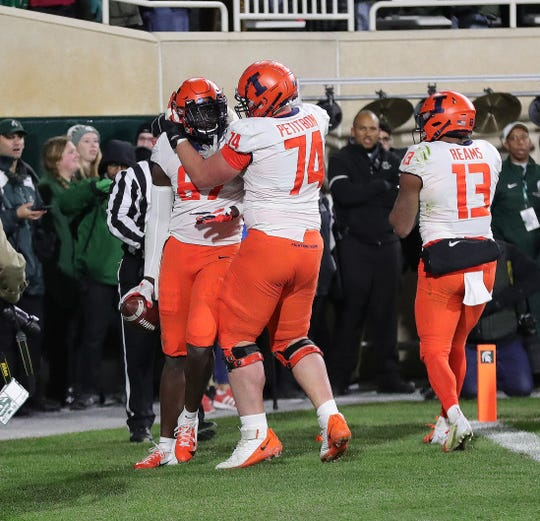 Illinois offensive lineman Richie Petitbon (74) congratulates tight end Daniel Barker (87) after his touchdown with 5 seconds left upset Michigan State, 37-34, Saturday, Nov. 9, 2019 at Spartan Stadium.