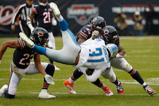 Lions running back Ty Johnson (31) is brought down by Bears cornerback Kyle Fuller (23), linebacker Danny Trevathan (59) and Leonard Floyd (94) during the first half Sunday.