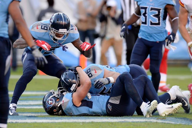 Titans tight end Anthony Firkser (86) and wide receiver Tajae Sharpe (19) celebrate with wide receiver Adam Humphries, on the ground, after Humphries scored the winning touchdown against the Chiefs in the fourth quarter on Sunday.