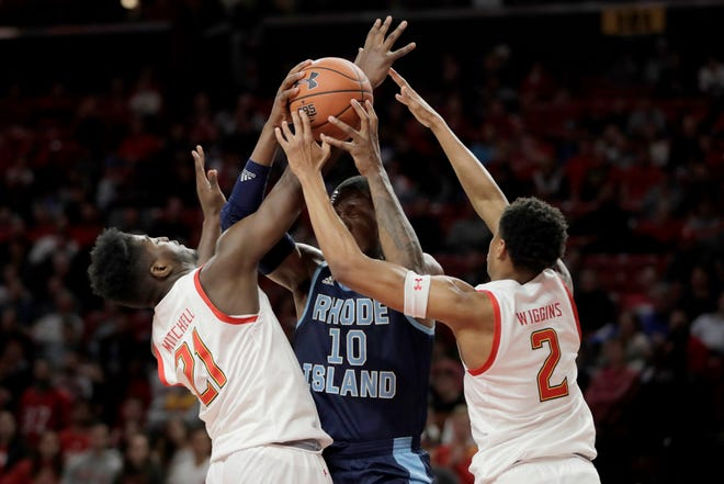 Rhode Island forward Cyril Langevine (10) tries to go up for a basket as Maryland forward Makhi Mitchell (21) and guard Aaron Wiggins (2) defend.