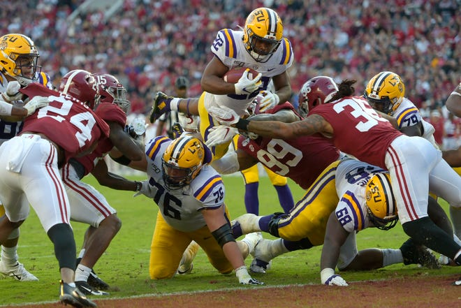 LSU running back Clyde Edwards-Helaire (22) dives over Alabama's Raekwon Davis (99) and Markail Benton (36) to score a touchdown in the first half on Saturday.