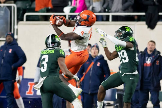 Illinois wide receiver Josh Imatorbhebhe makes a reception while under coverage from Michigan State safety Xavier Henderson, left, and cornerback Shakur Brown in the fourth quarter.