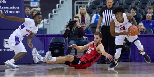 Evansville's DeAndre Williams (13) heads for a fast break as Ball State's Kyle Mallers (14) reaches to slow him down at Ford Center in Evansville Saturday night, Nov. 9, 2019.