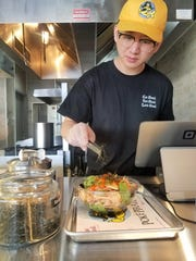 Jun Cao finishes a poké bowl with nori seaweed at the Poké Pirate.